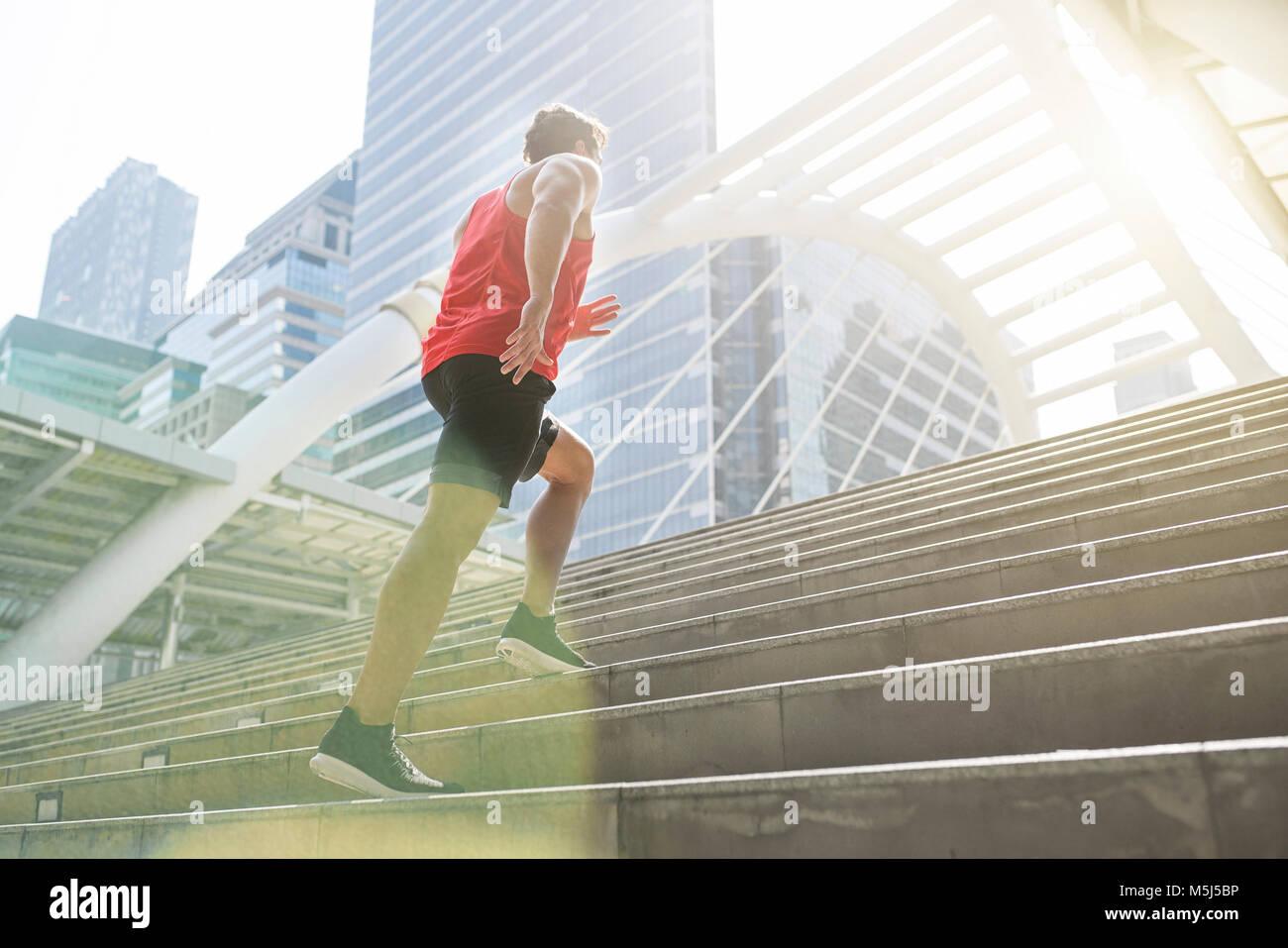 Man in red fitness shirt running upstairs in the city - Stock Image