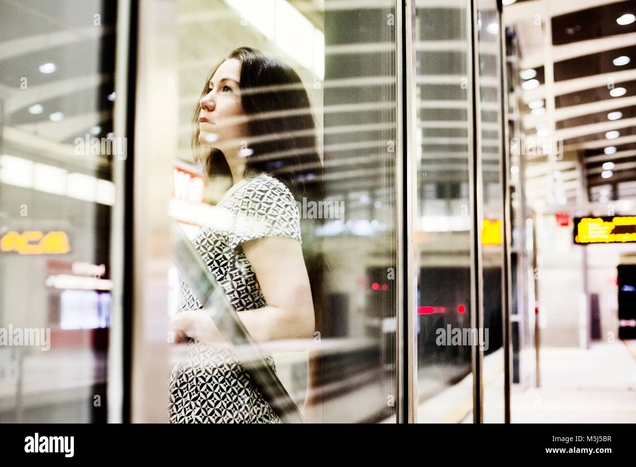 Portrait of young woman waiting behind glass wall on underground station platform - Stock Image