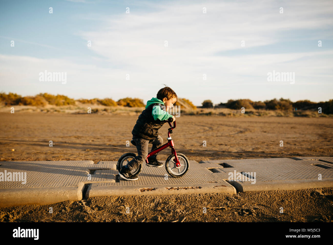Boy running with a bike on the beach in winter - Stock Image
