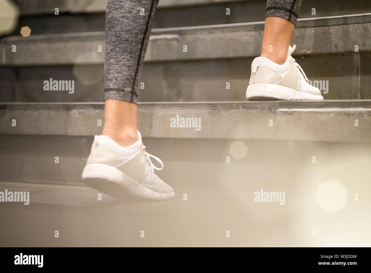 Close up of female legs with white sport sneakers running up the stairs - Stock Image