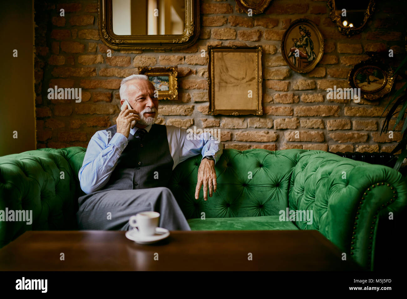 Elegant senior man sitting on couch in a cafe talking on cell phone Stock Photo