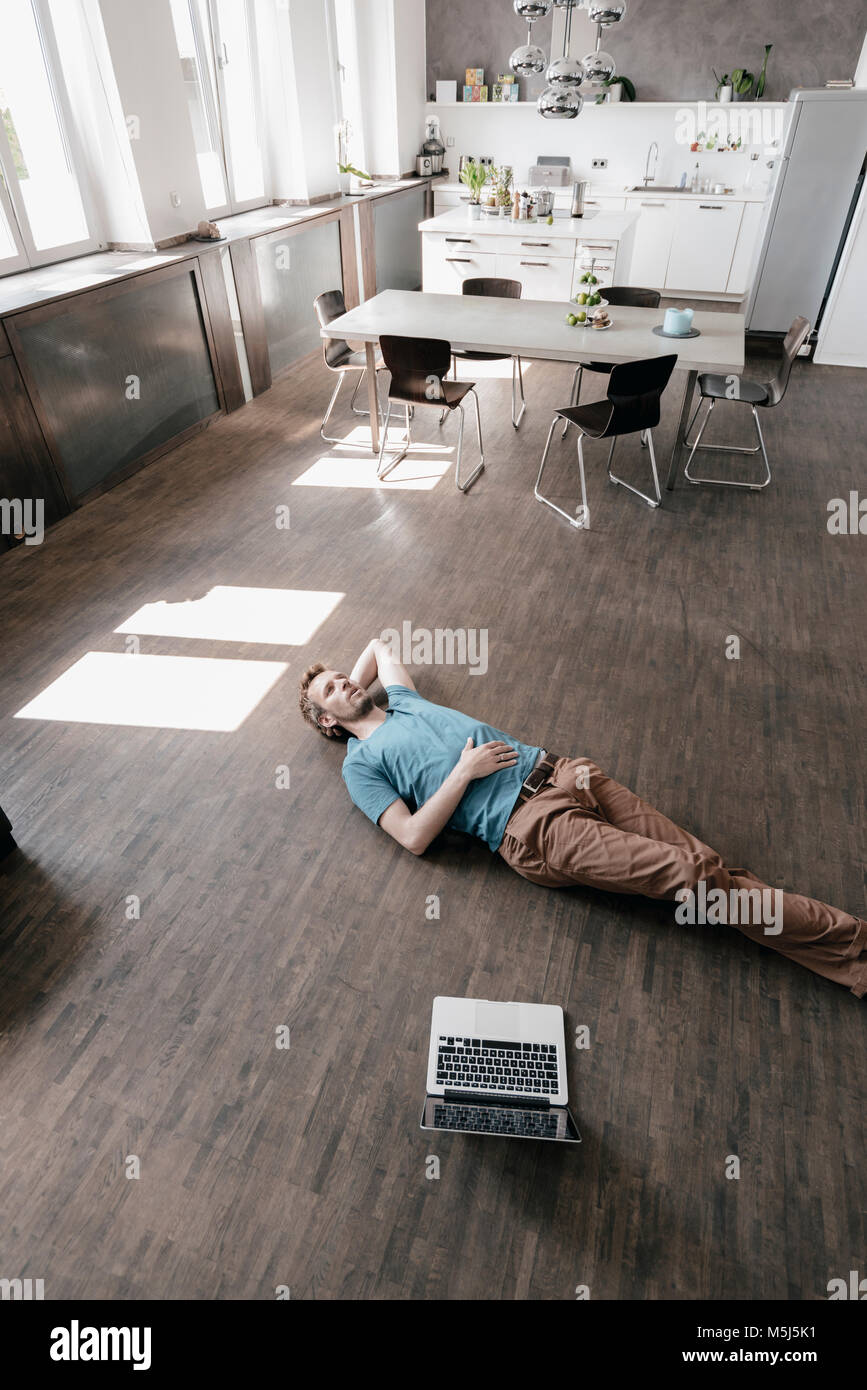 Pensive man lying on the floor in a loft - Stock Image