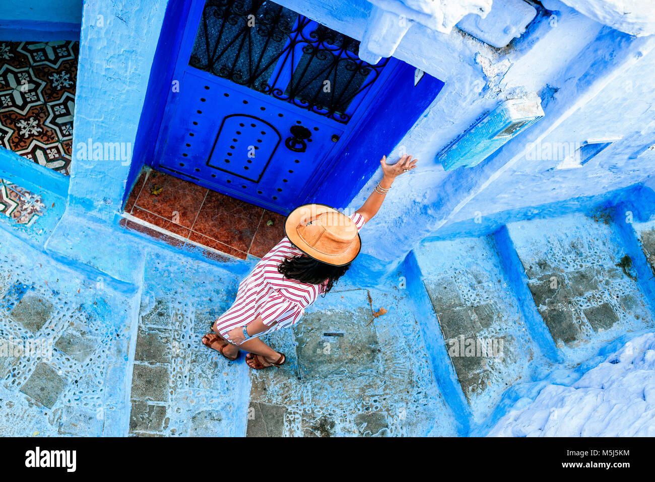 Morocco, Chefchaouen, woman walking alley downwards, top view - Stock Image
