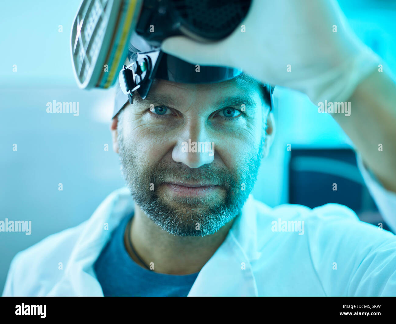 Portrait of man removing respirator - Stock Image