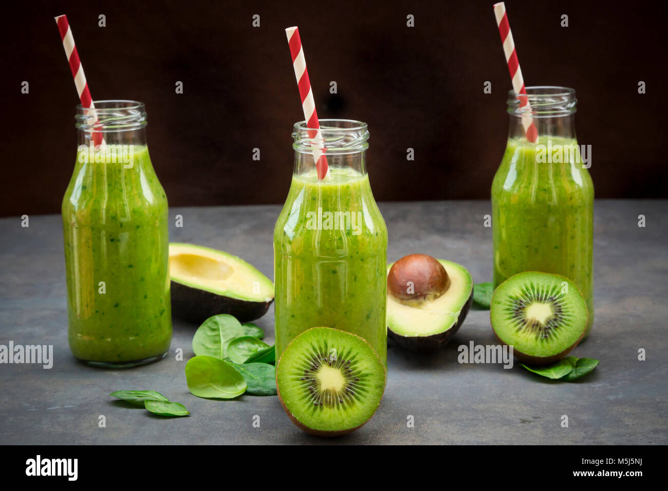 Green detox smoothie with avocado, kiwi and baby spinach - Stock Image
