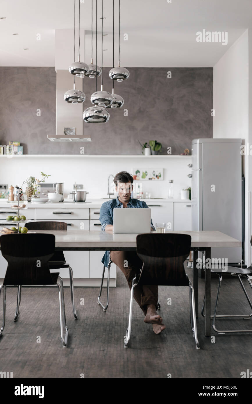 Young man sitting at table in the kitchen working on laptop Stock Photo