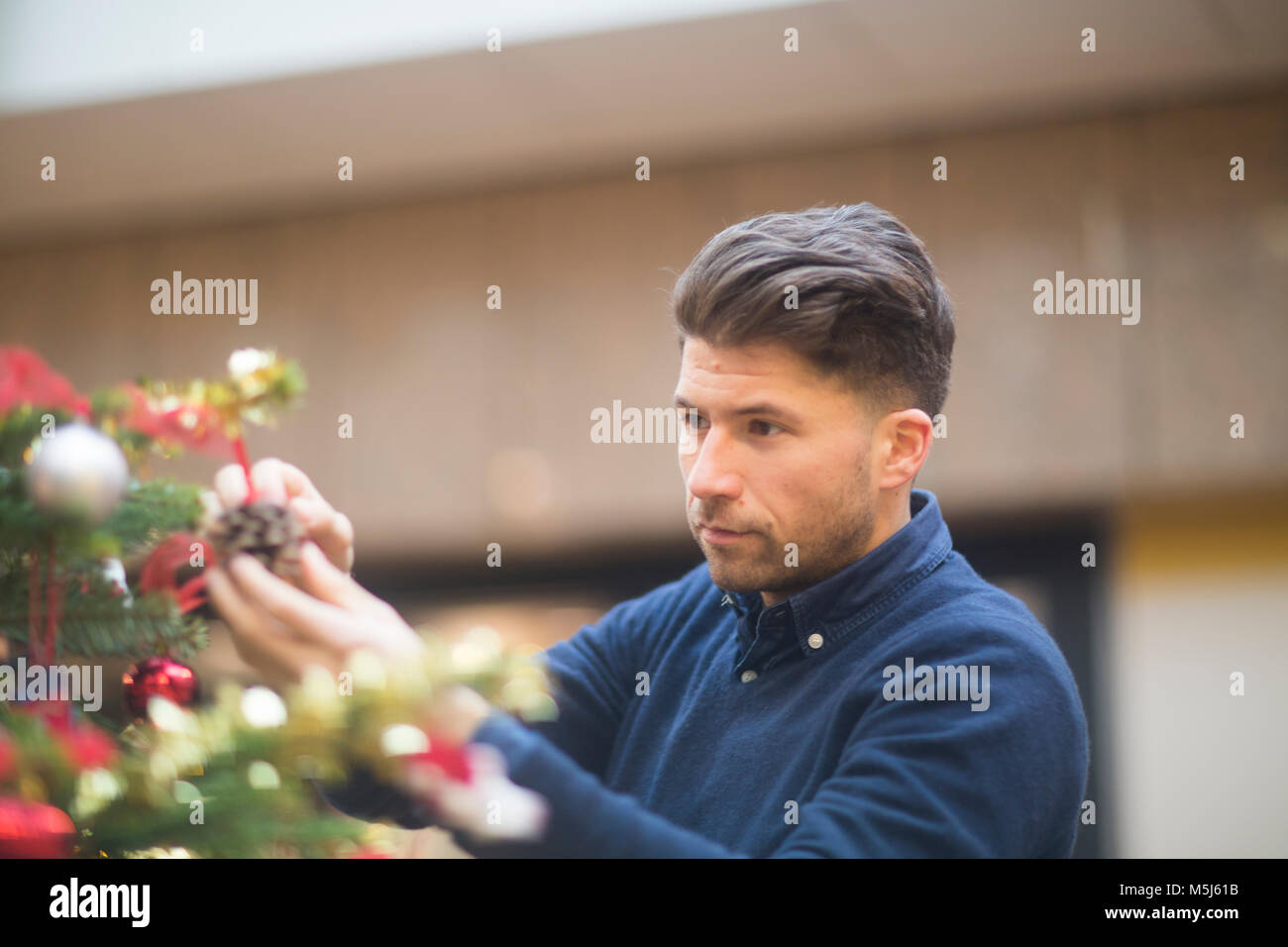 Portrait of man looking at Christmas decoration in a shopping mall - Stock Image