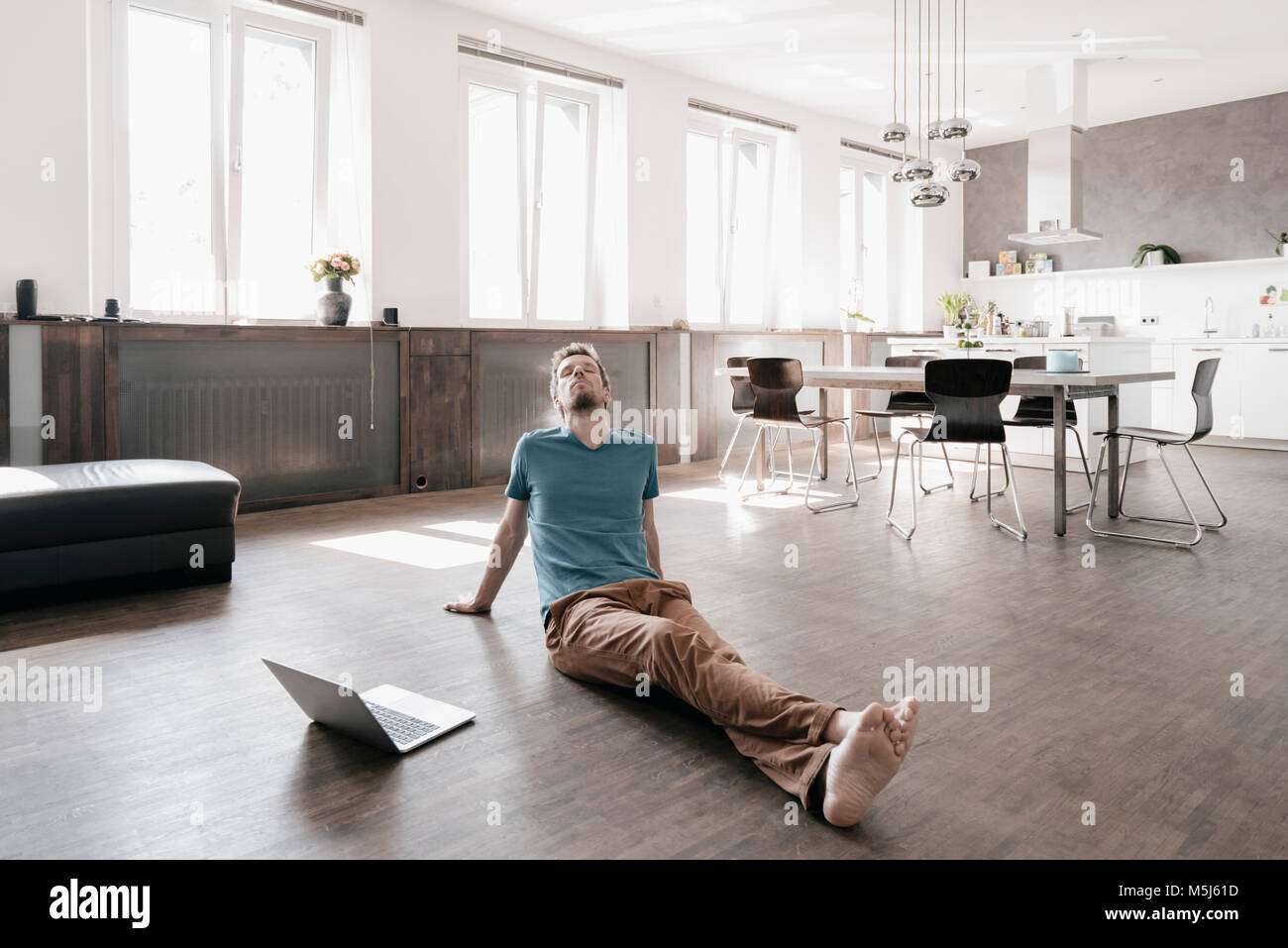 Man with eyes closed sitting on the floor in a loft relaxing - Stock Image
