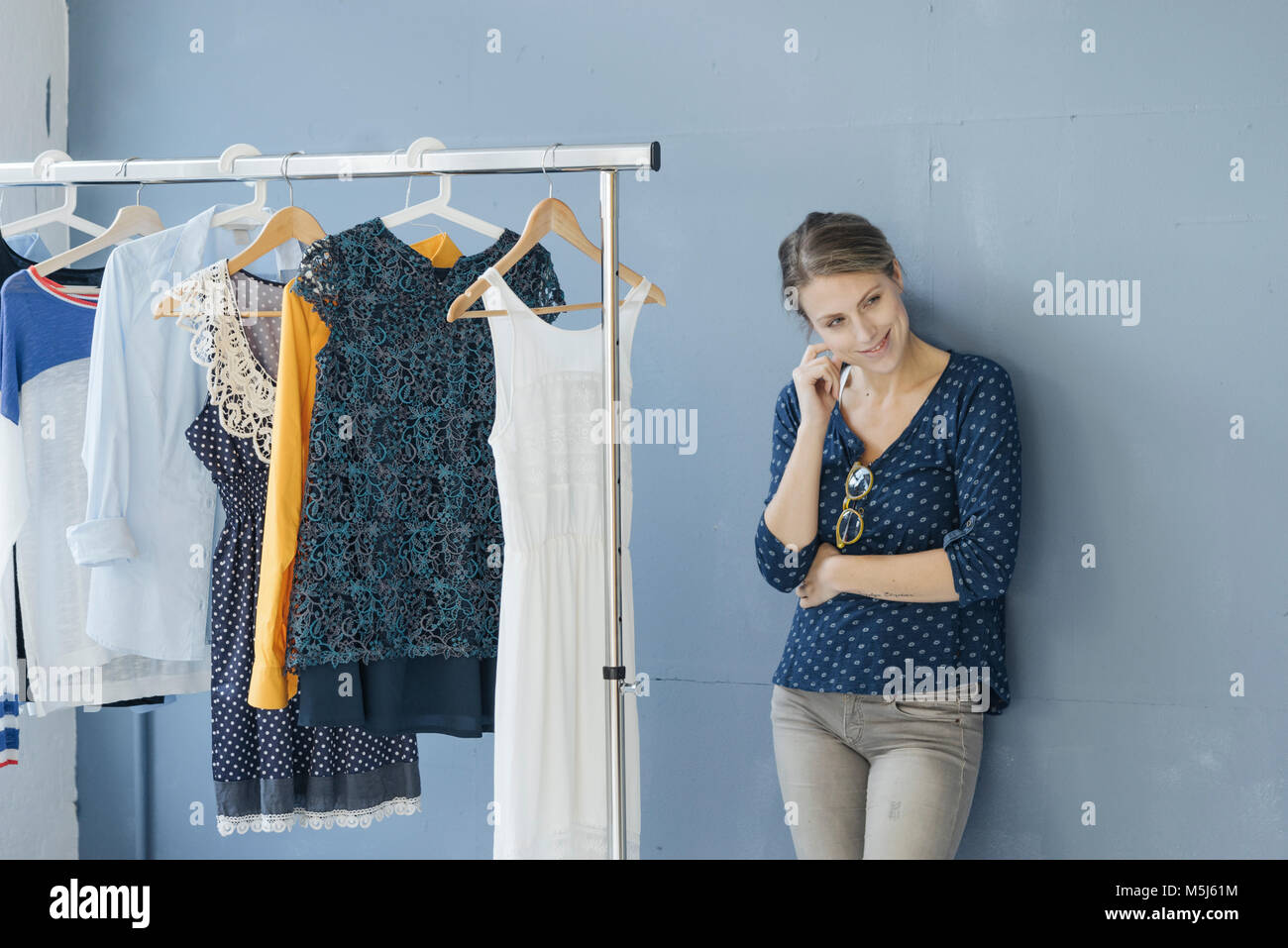 Portrait of smiling fashion designer in her studio leaning against wall - Stock Image