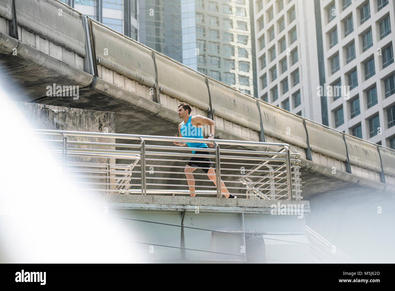 Runner in blue fitness shirt running over modern bridge - Stock Image