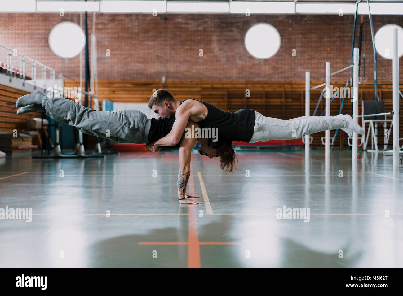 Two men doing acrobatics in gym - Stock Image