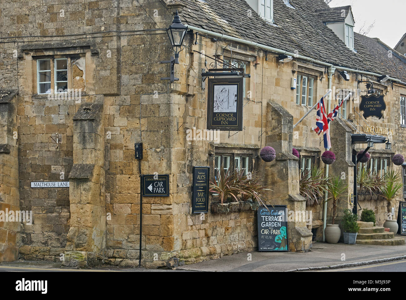 The Corner Cupboard Inn in the Cotswold market town of Winchcombe, with an array of signs and flags outside the - Stock Image