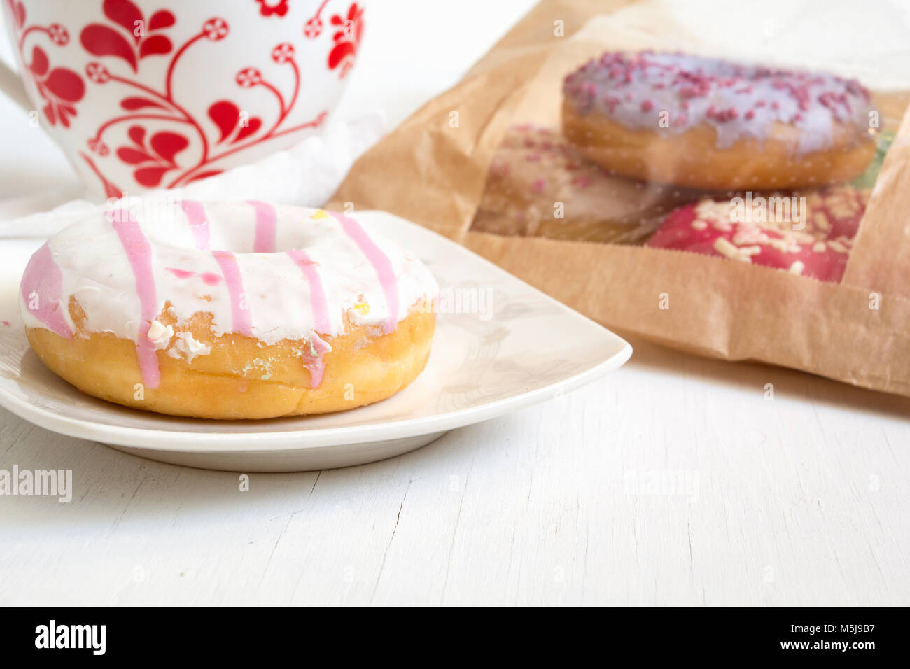 Donut on plate. Bag full of doughnuts and cup of tea. - Stock Image
