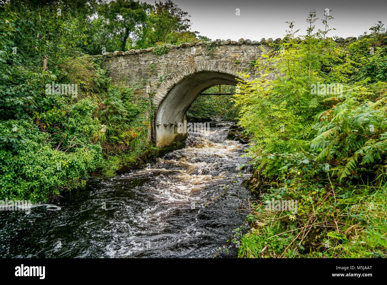 An old single-lane bridge over a river near Carrick in County Donegal Ireland. - Stock Image