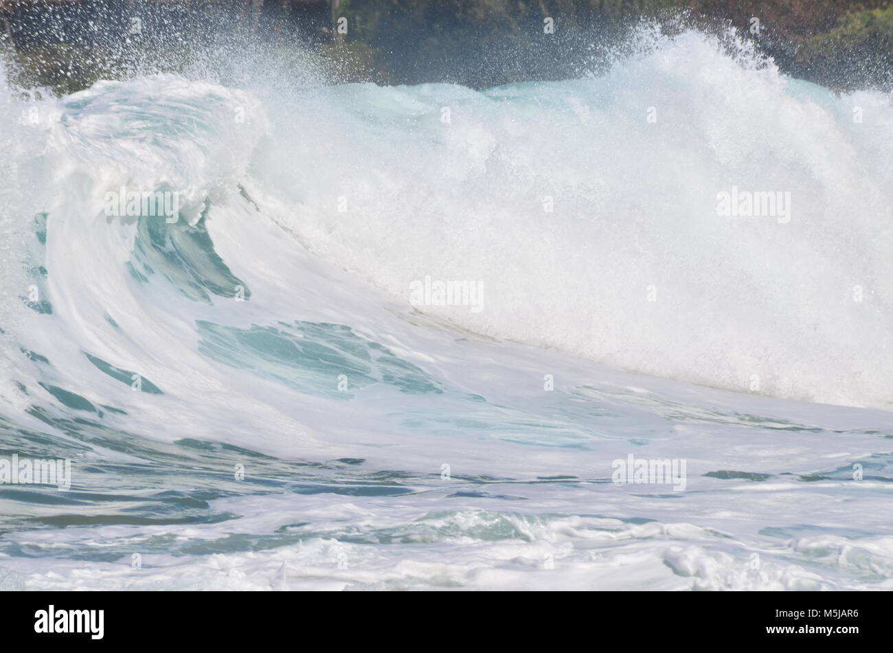 Crashing waves at a beach in Hawaii, during a tropical storm and high tide - Stock Image
