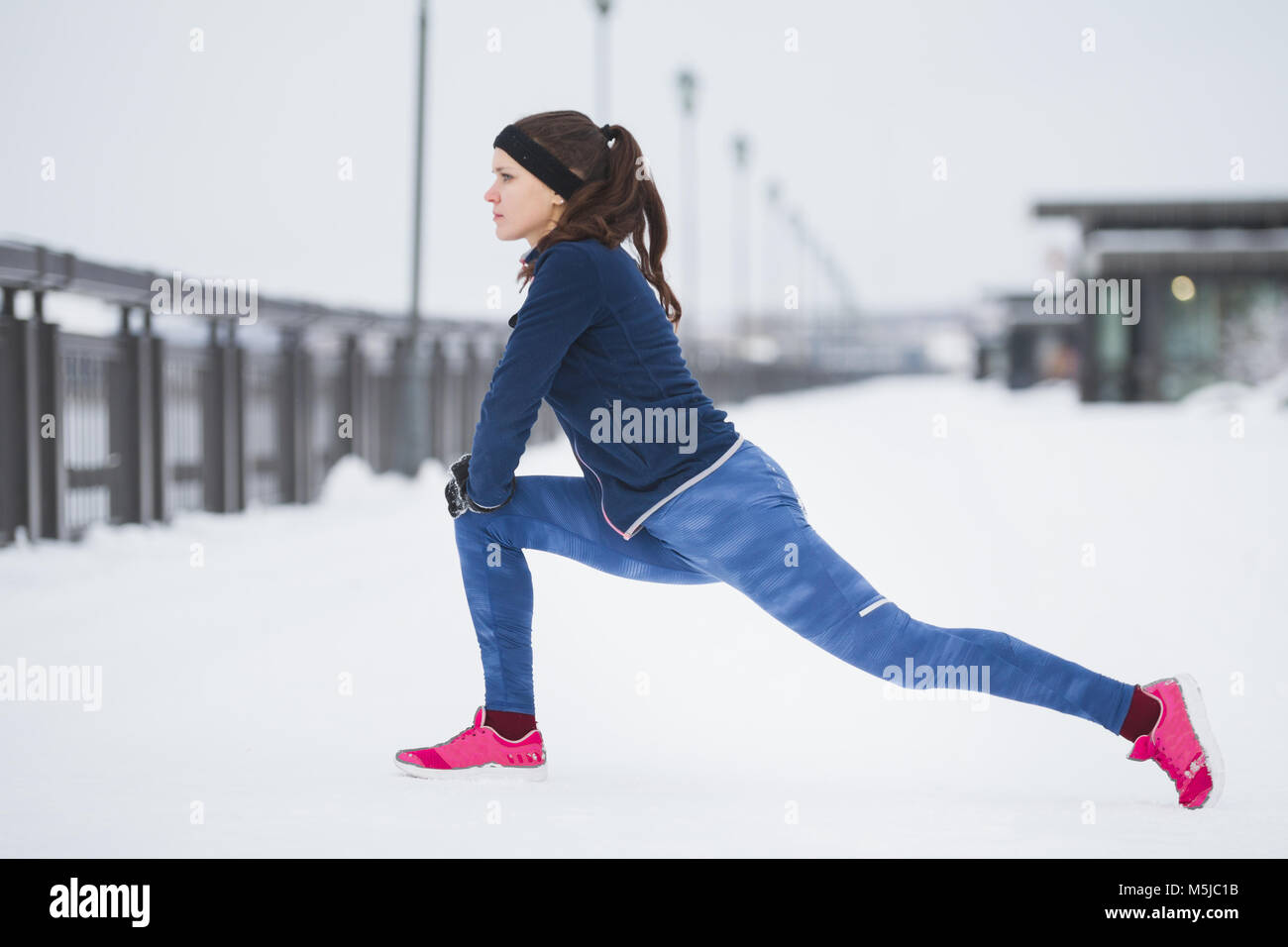 Young woman runner doing flexibility exercise for legs before run at snow winter promenade, - Stock Image