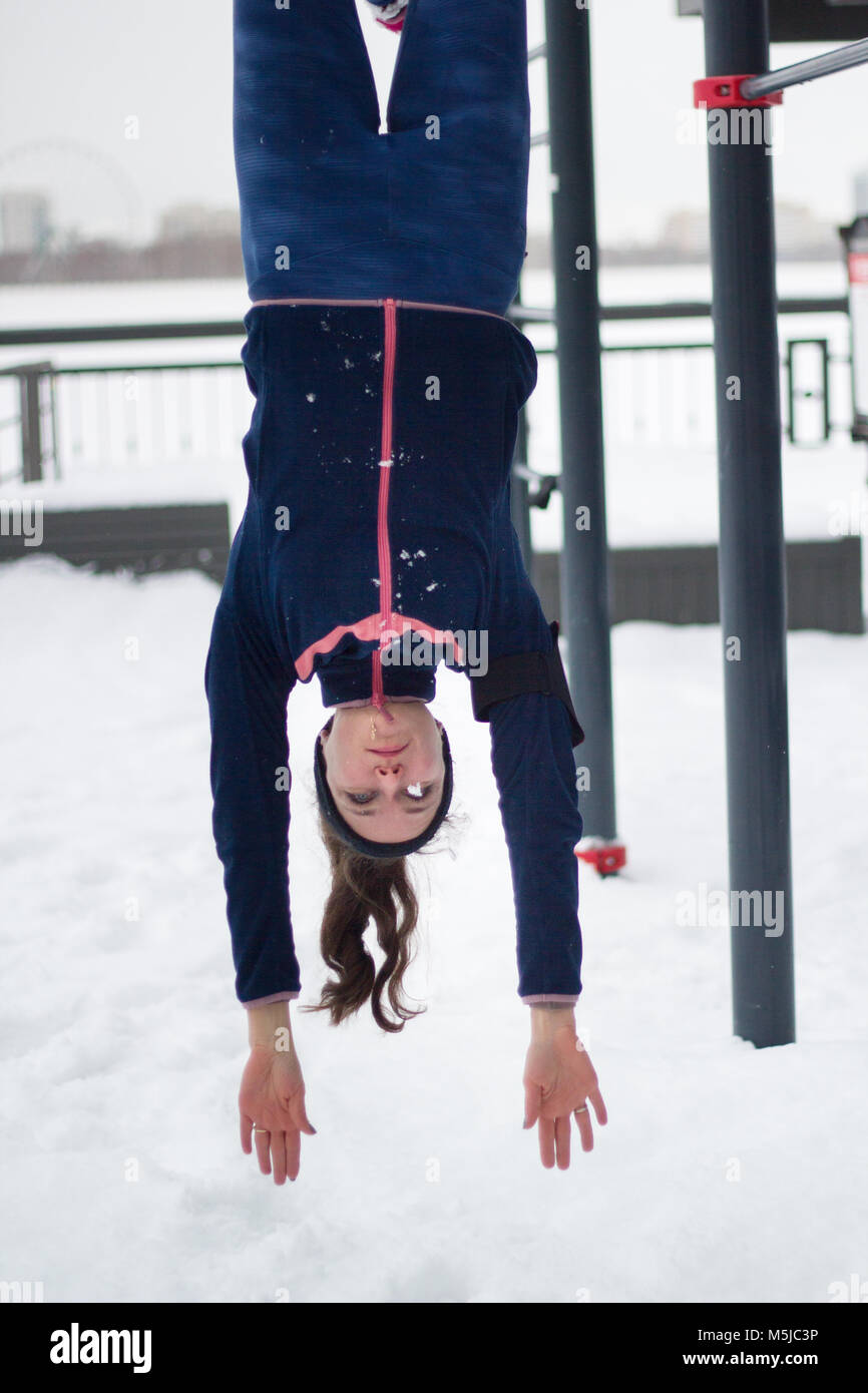 Young Sport Woman Hanging Upside Down Strength Exercises On Work Out Fitness At Snow Winter Park