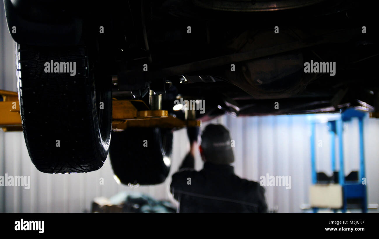 Car service - mechanic unscrewing automobile parts while working under a lifted auto - Stock Image