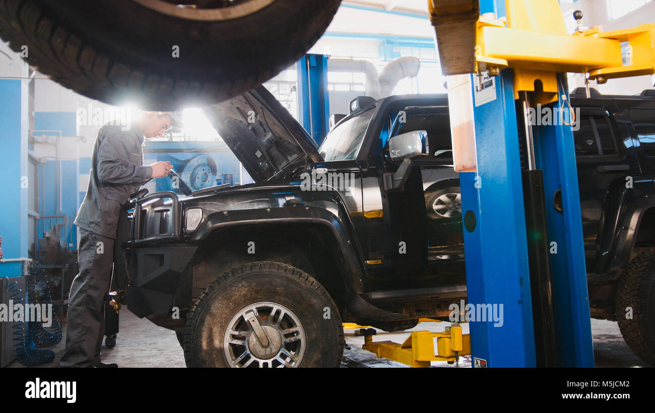 Luxury SUV standing in the garage for repairing - mechanic working - Stock Image