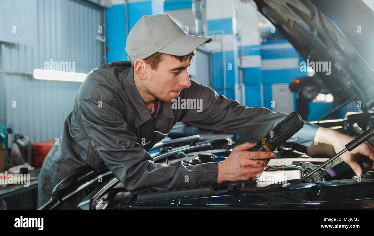 Mechanic in overalls looking to hood of the car - automobile service repairing - Stock Image