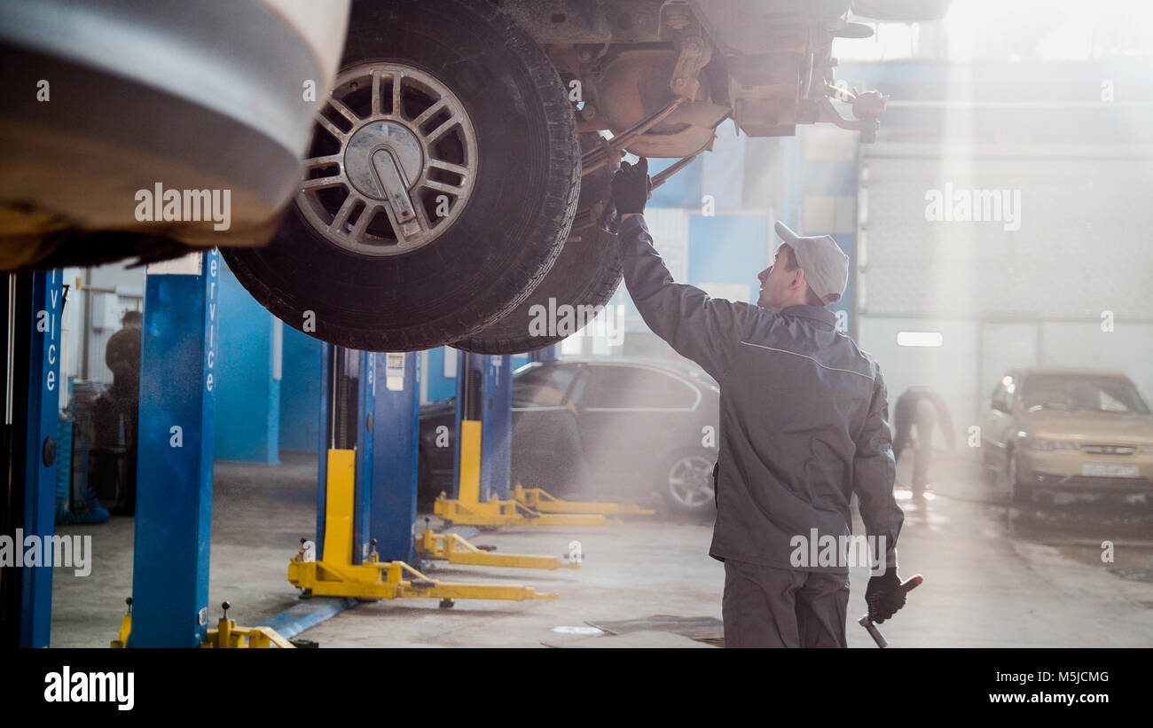 Garage automobile service - a mechanic checks the transmission - Stock Image
