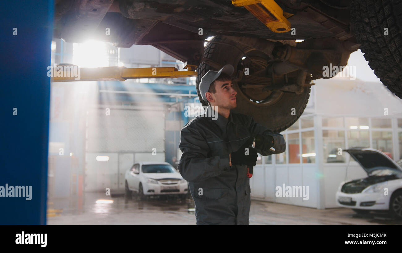 Garage automobile service - a mechanic under bottom of car checks the wheel - Stock Image