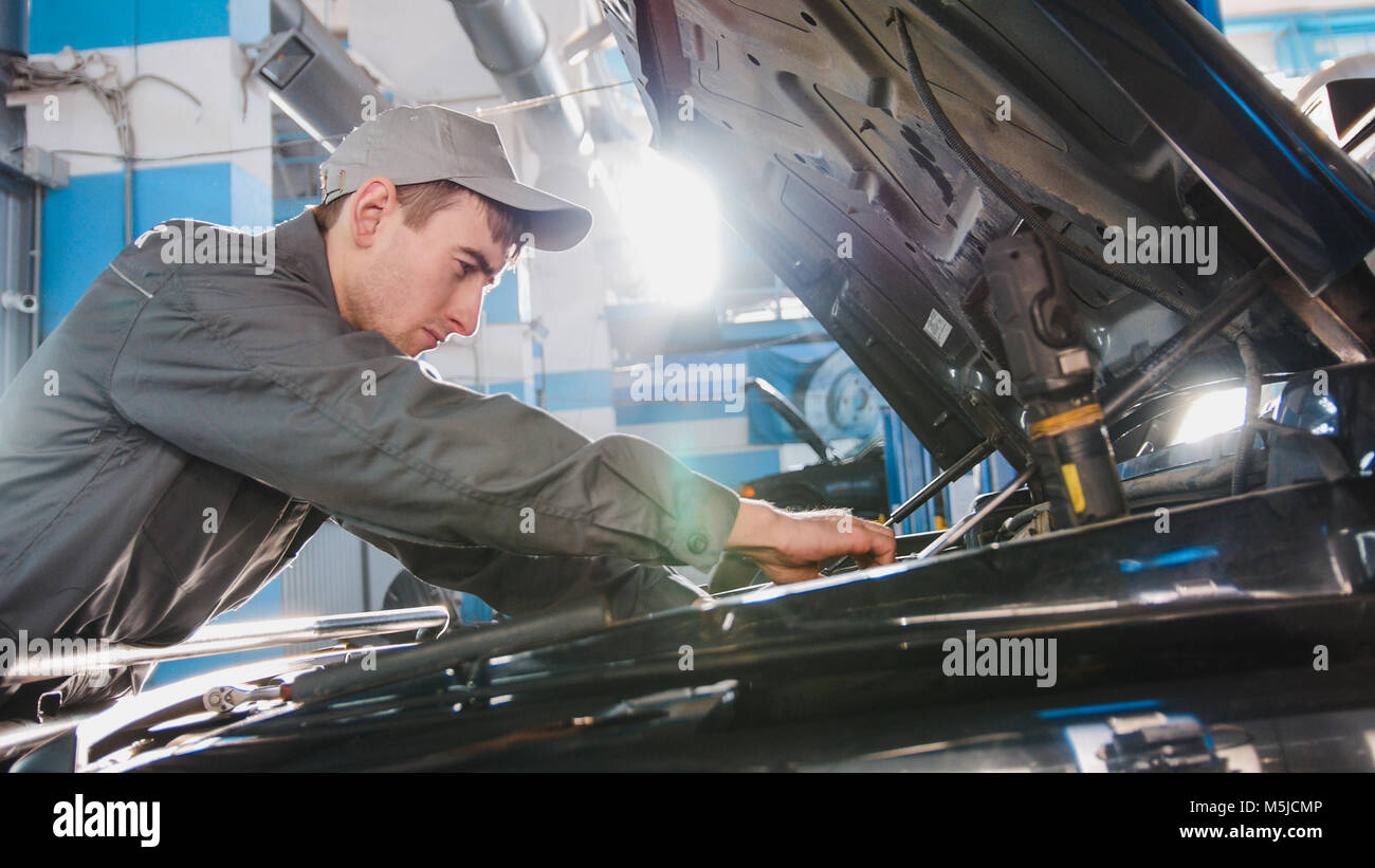 Mechanic male in automobile garage checking hood of the car for luxury SUV - Stock Image