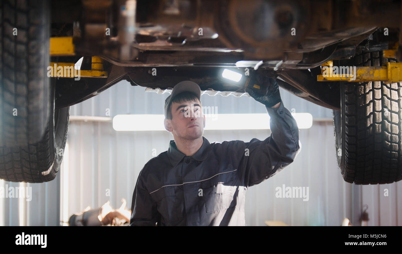 Mechanic with thr lamp is checking the bottom of car in garage automobile service, wide angle - Stock Image