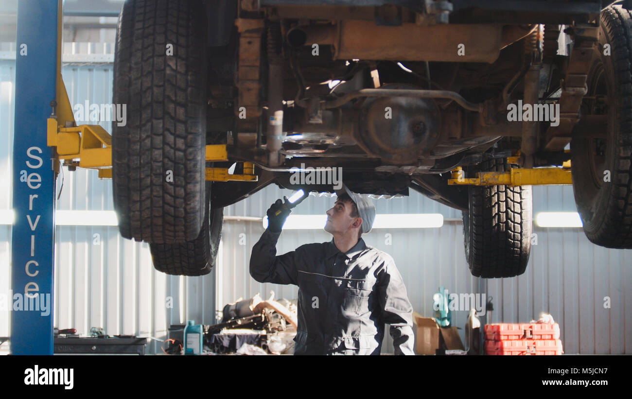 Mechanic with thr lamp is checking the bottom of SUV car in garage automobile service, wide angle - Stock Image
