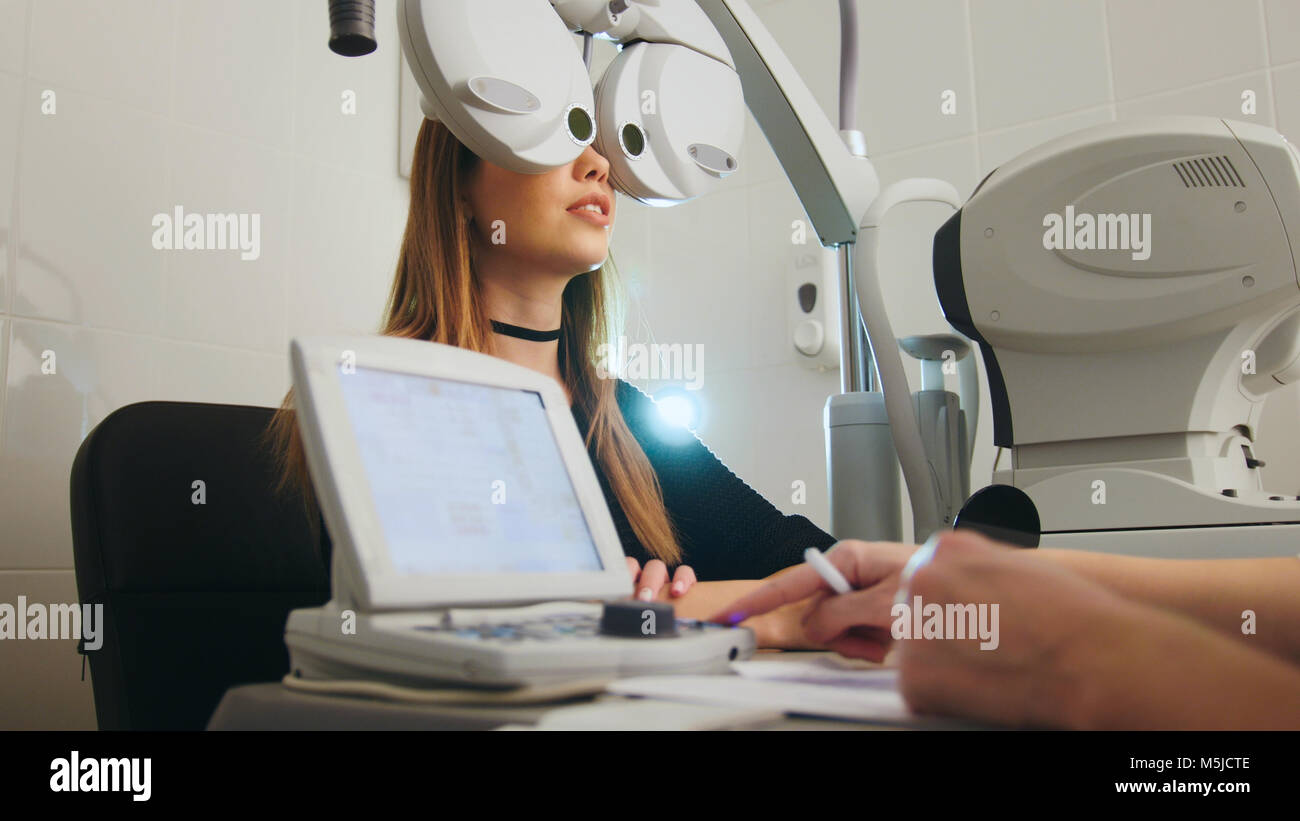 Blonde young female doing eye test with optometrist in medical center - Stock Image