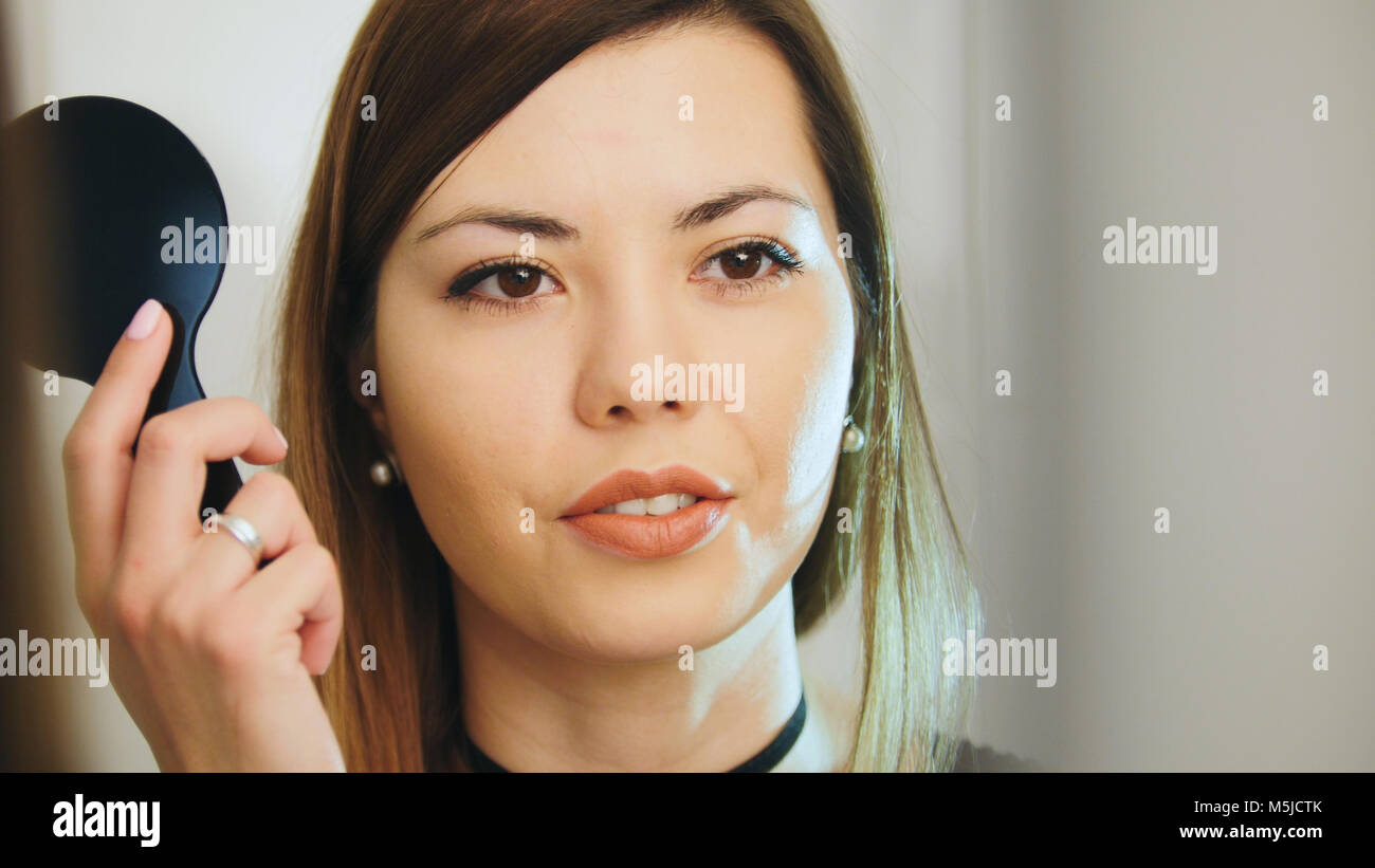 Ophthalmology medical, concept - beautiful female checks vision in an ophthalmologist room - short-sighted and squints - Stock Image