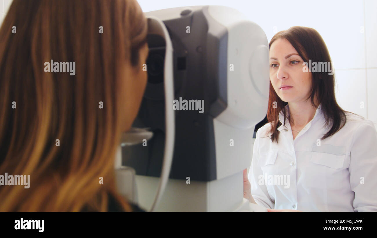 Ophthalmology clinic - optometrist checks patient's vision by modern electronic machine - Stock Image