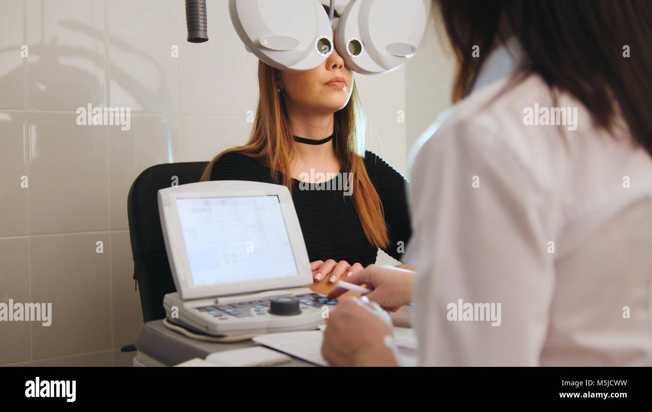 Ophthalmology - eyes clinic concept - optometrist and patient doing exam vision - Stock Image