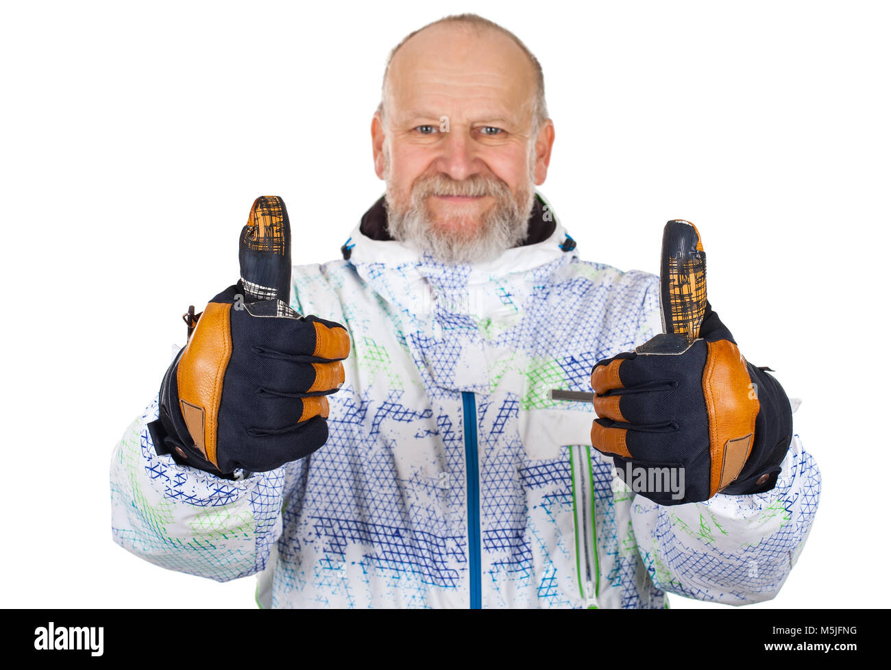 Cheerful elderly man in ski suit showing thumbs up on isolated background - Stock Image