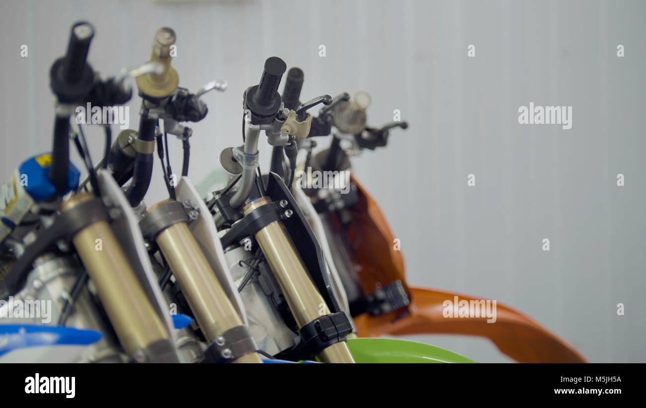 Several motorcycle in the garage - handlebars of enduro cross motorbike - Stock Image