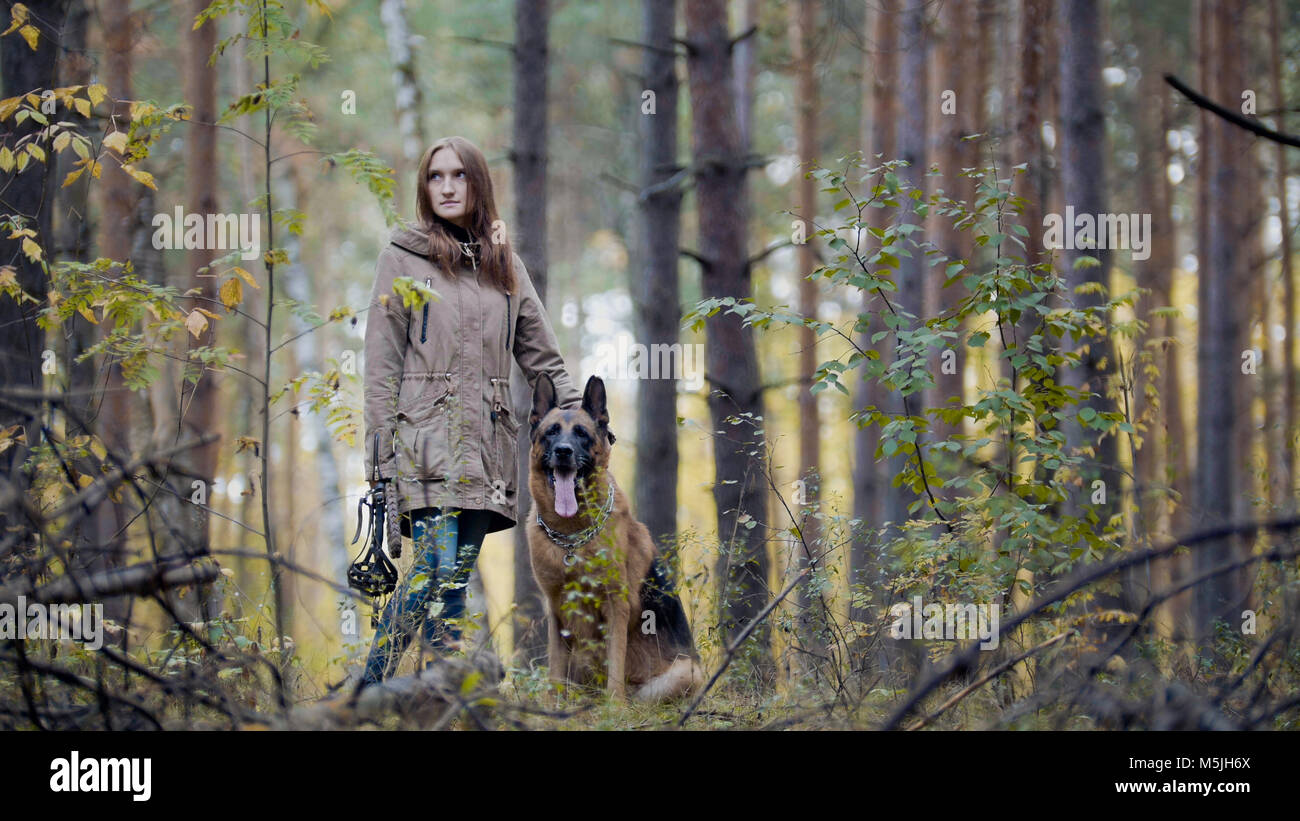 Young attractive girl and her pet - german shepherd - walking on a autumn forest - Stock Image