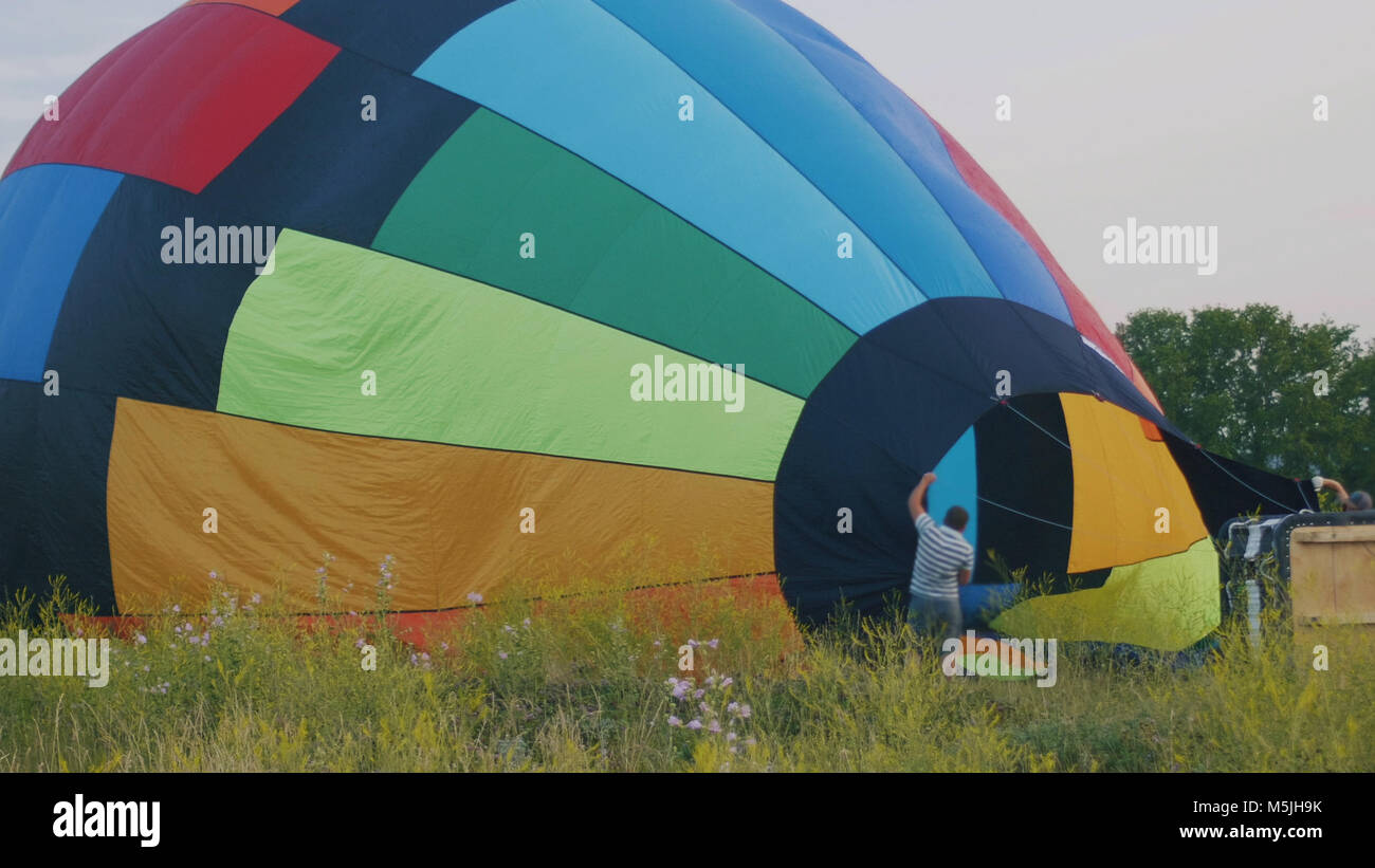 Crew inflate a big colorful hot air balloon at summer field Stock Photo