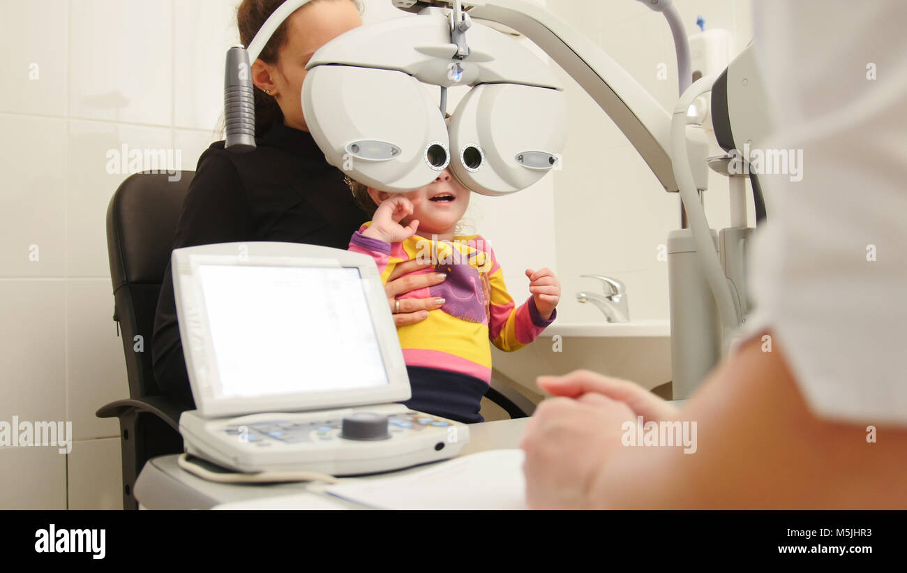 High tehnology in medicine - optometrist in clinic checking little girl's vision - children's ophthalmology - Stock Image