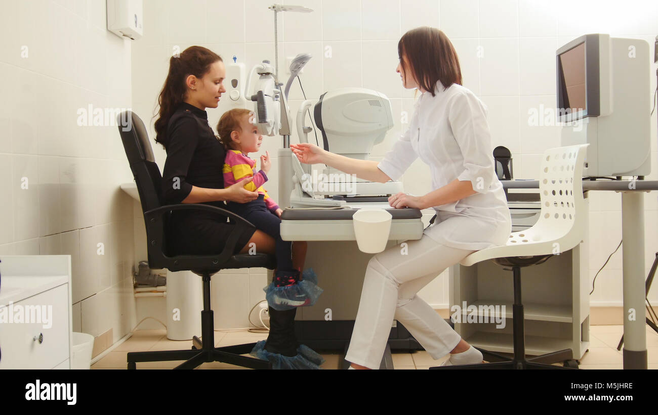 Mother and child in the ophthalmologist's room- optometrist in clinic checking little child's vision - Stock Image