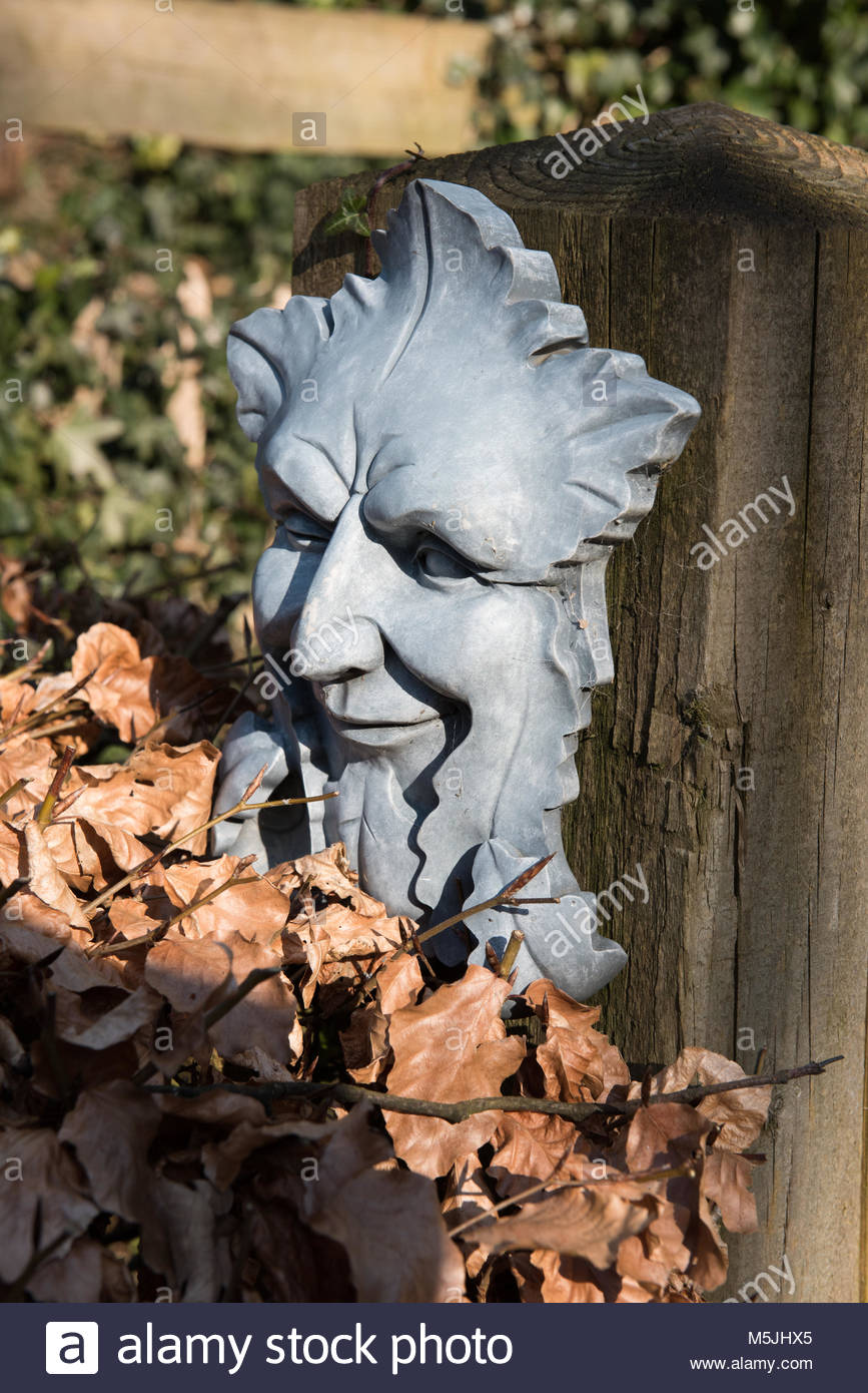 Green man plaque on a gate post - Stock Image