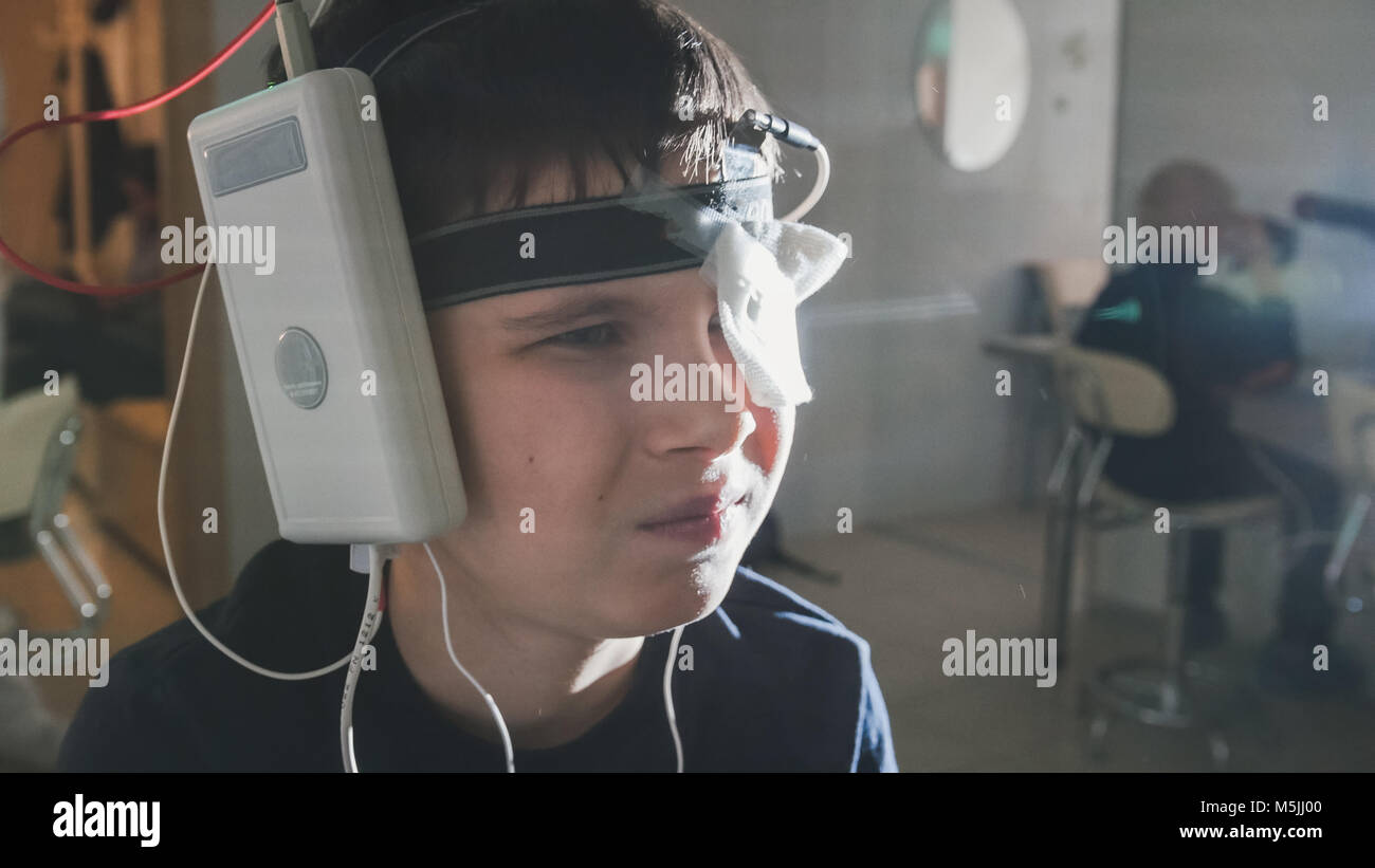 Teenager boy with electrodes on the head looking to monitor - healthcare children's diagnostic - Ophthalmology researching Stock Photo