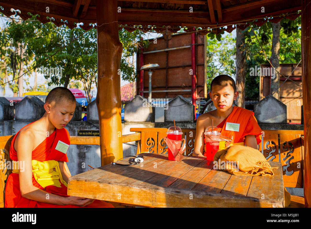 LAMPANG, THAILAND FEBRUARY 21, 2017 - A couple of young monks sit and rest outside the temple. - Stock Image