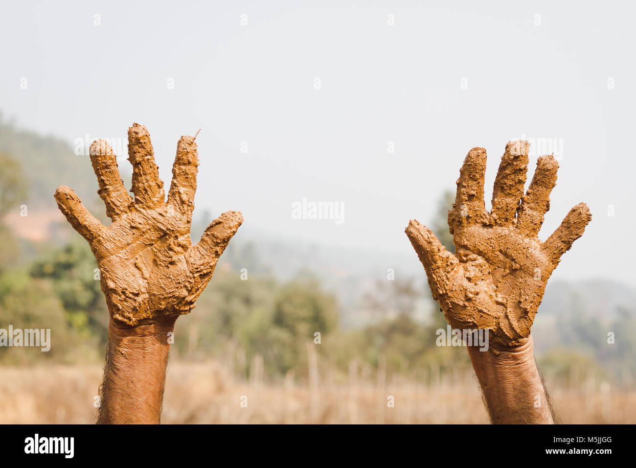 Unidentified Worker showing his muddy hands, Dirty Hands. - Stock Image