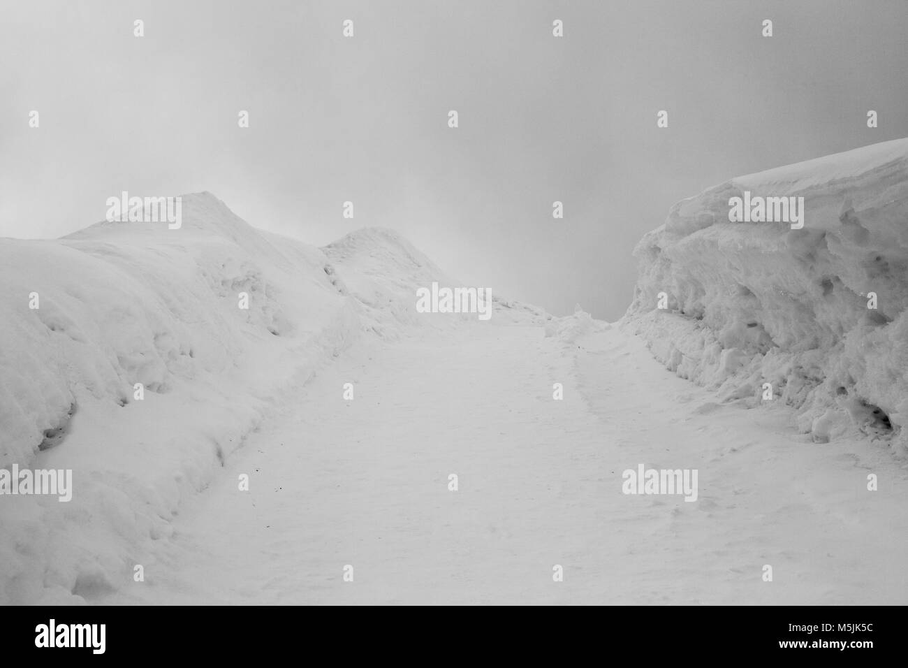 An amazing view of snow covered landscape, mountains and a ski piste in the alps switzerland in winter - Stock Image