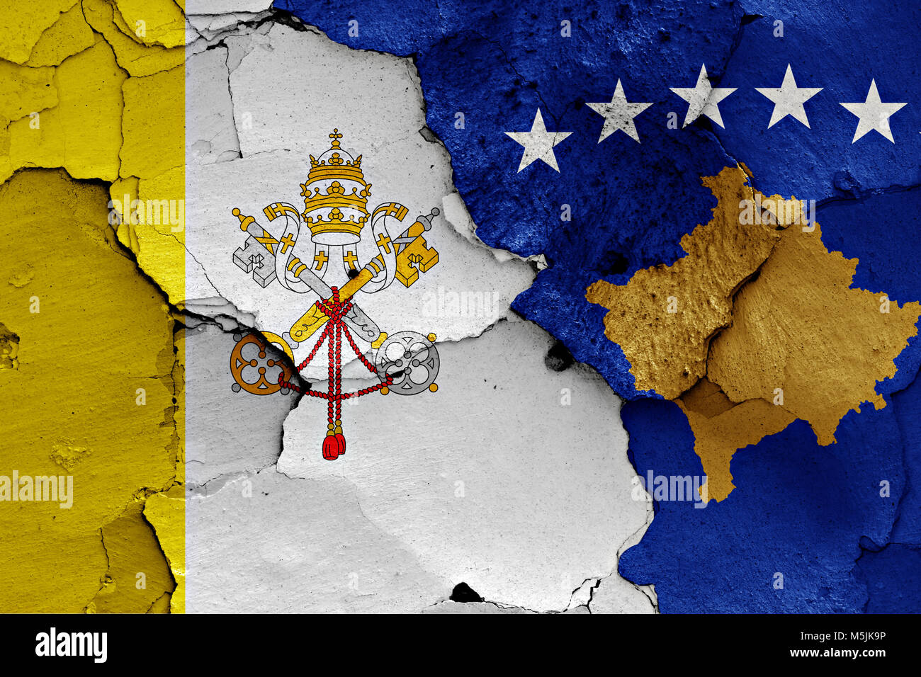 flag of Vatican and Kosovo painted on cracked wall - Stock Image