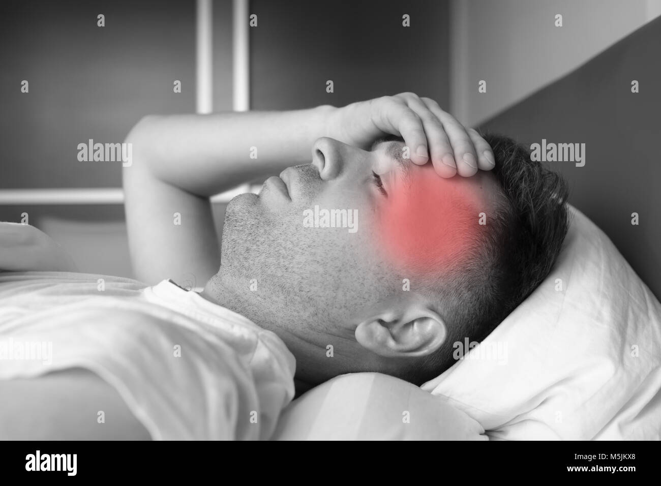 man lying in bed at home suffering from headache or hangover Stock Photo