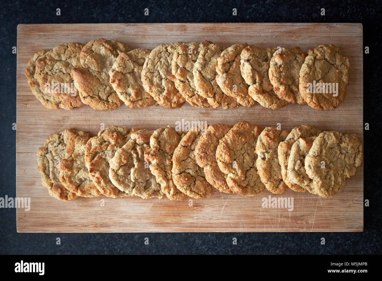 Two rows of freshly cooked plain American cookie biscuits laid out to cool on a wooden board. - Stock Image