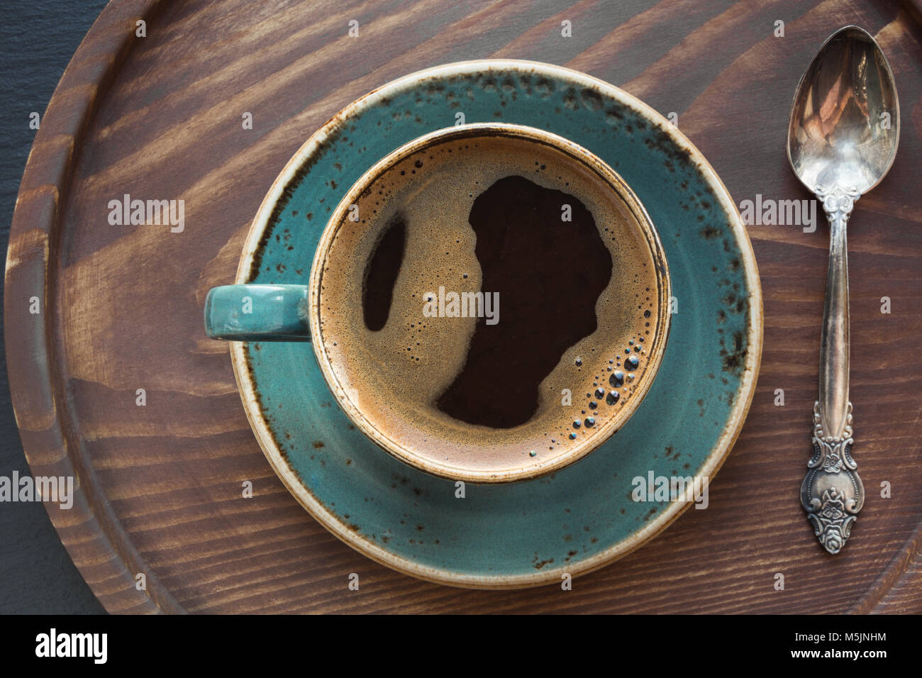 Cup of black coffee with coffee spoon on wooden tray. Top view. - Stock Image