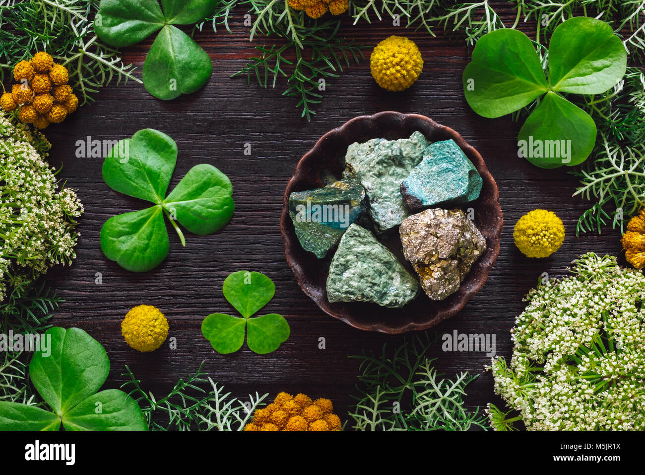 Ceramic Bowl of Green Aventurine and Pyrite with Shamrocks and Mixed Foliage on Dark Table - Stock Image