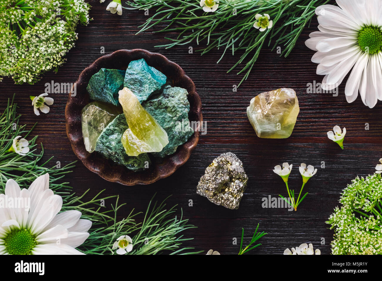Green Aventurine, Green Calcite and Pyrite with Mixed Botanicals on Dark Table - Stock Image
